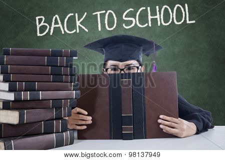 Learner With Mortarboard And Book In The Class