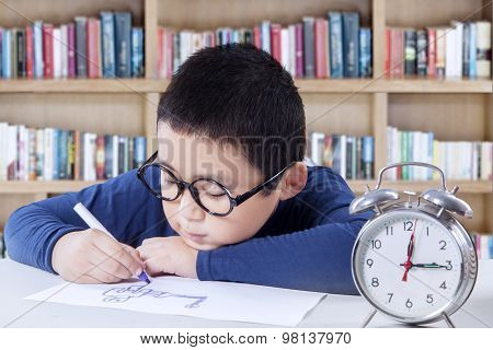 Little Boy Drawing In Library With A Clock On Desk