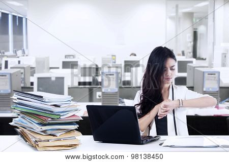 Overworked Businesswoman Looking At Watch
