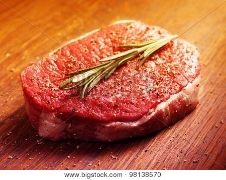fresh raw steak with pepper and rosemary on the wooden board.Filtered image: warm cross processed vintage effect.