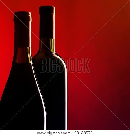 Bottles of red wine on dark red background. Filtered image: vintage effect.