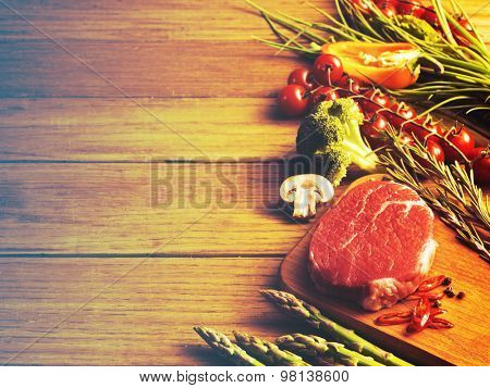 Raw steak on the wooden board.Filtered image: vintage effect.