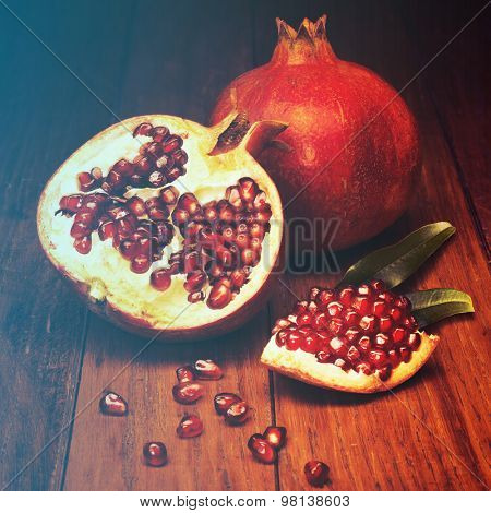 juicy pomegranate open on wood board.Filtered image: warm cross processed vintage effect.