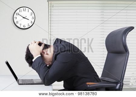 Stressful Manager In Office With Clock On The Wall