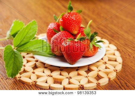 several strawberries on a plate on a table with leaf. close-up