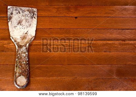 Rusty Dirty Spatula Scraper Toolon A Brown Wooden Background. Copy Space To Right.