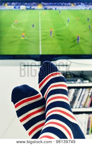 closeup of the feet of a man who is watching a soccer match in the TV, wearing striped socks