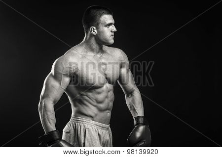 Strong boxer on a black background.