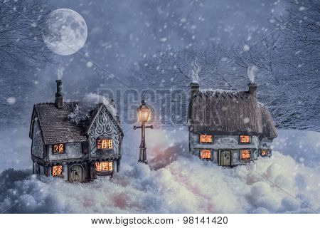 Winter cottages in country lane landscape at night with glowing lamp light