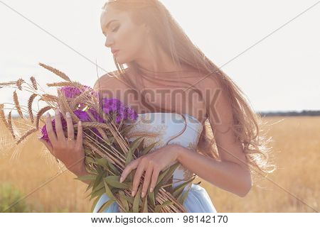 Beautiful sexy girl in a blue dress with long hair , holding a bouquet of ears and pink flowers stan
