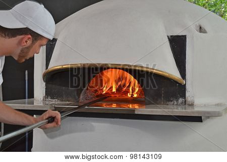 baker man cooking pizza on traditional wooden oven