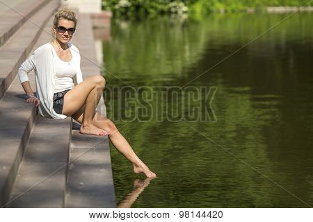 Young beautiful woman sitting on the waterfront pulls leg to water.