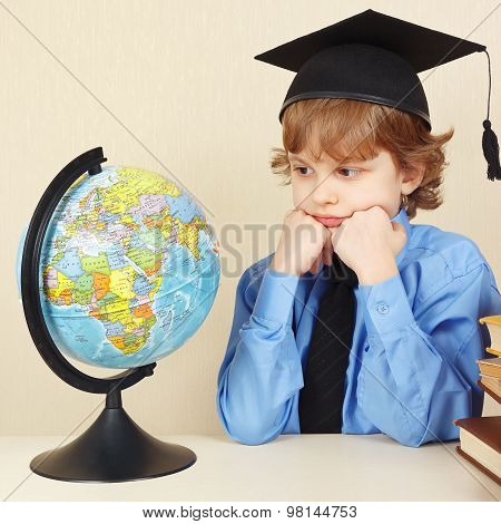 Little serious boy in academic hat looks at globe