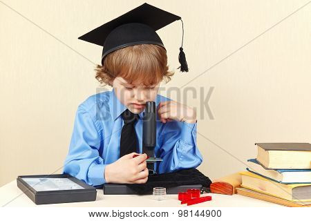 Little serious boy in academic hat looking through microscope at his desk
