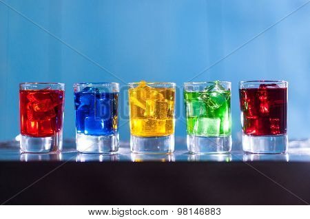Bright alcohol drinks or berries cocktail in different colours, glasses tumbler on wooden backfround
