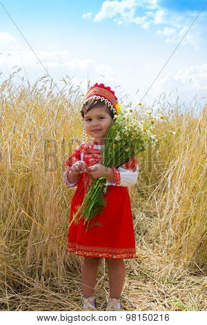 Little Girl In The Russian National Sundress With A Bouquet Of Camomiles