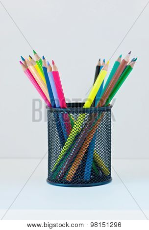 Pencils in a case on the light-coloured shelf