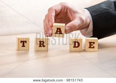 Closeup Of Businessman Or Broker Placing A Letter A In A Line Of Wooden Cubes Reading Trade