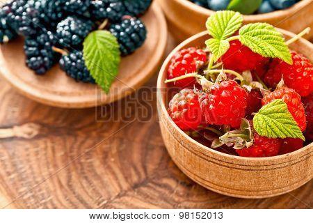 Ripe raspberries with green leaves macro