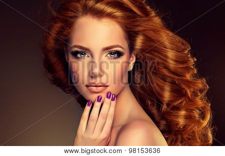 Girl model with long curly red hair . Trendy image of a red head woman