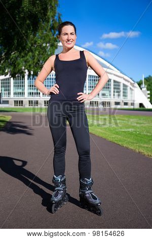 Happy Young Brunette Woman On Roller Skates In Park