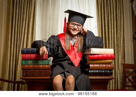 Girl In Graduation Cap Sitting On Table And Leaning On Book