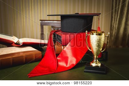 Graduation Hat, Red Ribbon And Golden Cup For First Place