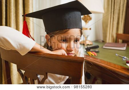 Thoughtful Little Girl In Graduation Hat Posing On Chair