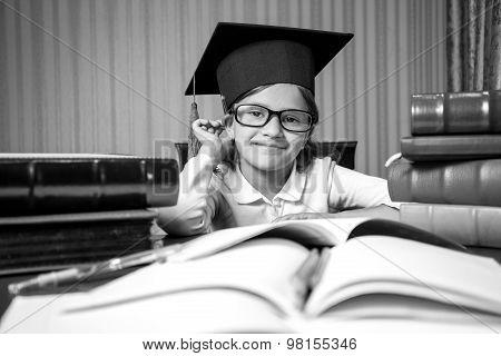 Portrait Of Smart Girl In Graduation Hat Sitting At Desk Full Of Book