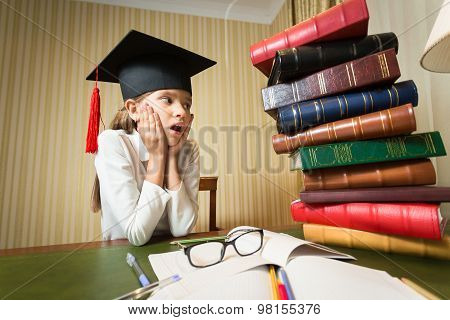 Girl In Graduation Cap Looking At High Heap Of Book On Table At Library