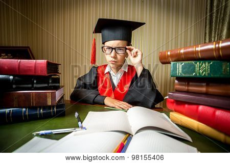 Smart Girl In Graduation Cap And Gown Looking At Camera