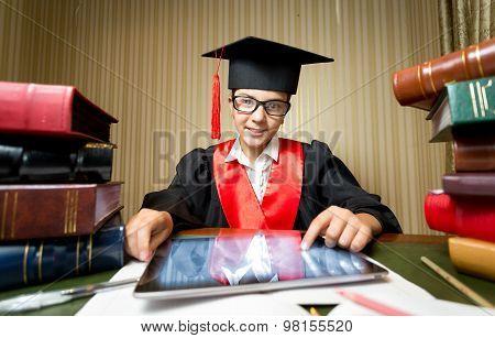 Smiling Girl In Graduation Cap Using Digital Tablet At Library