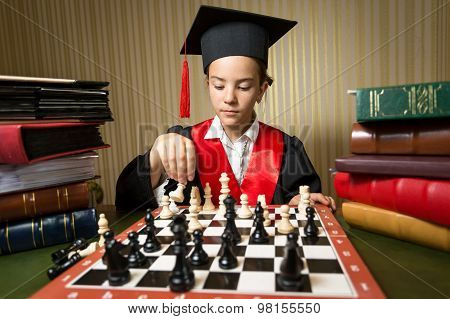 Portrait Of Smart Girl In Graduation Cap Playing Chess