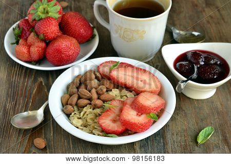 Oatmeal porridge, fresh strawberries, almonds and jam