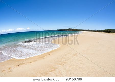 A beautiful white sand beach with clear blue water on a remote beach in Molokai Hawaii.
