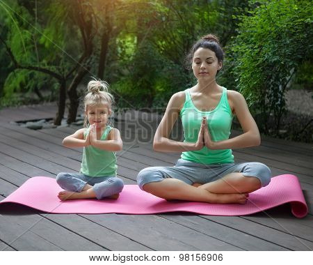 Mother And Daughter Doing Exercise Practicing Yoga Outdoors