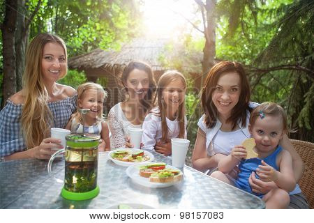 Happy Mothers And Her Adorable Little Daughters At Outdoors Cafe