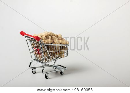 unshelled peanuts in the supermarket trolley, isolated on white background
