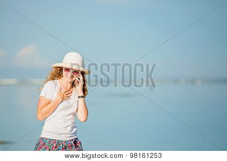 Beautiful young woman at the beach talking on mobile phone and laughing