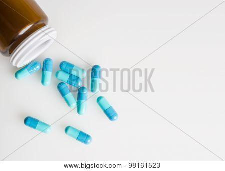 Glass Medical Bottle And Blue Medicine Capsules, Pills Are Spilled On The White Surface