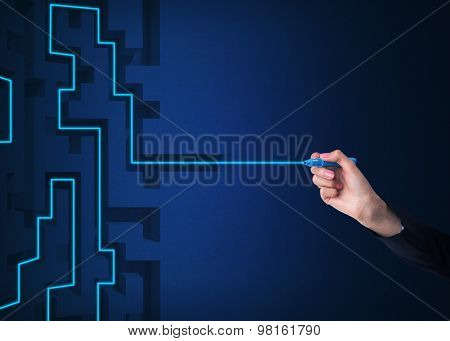 A Hand Is Drawing A Line As A Maze Solution. Dark Blue Background.
