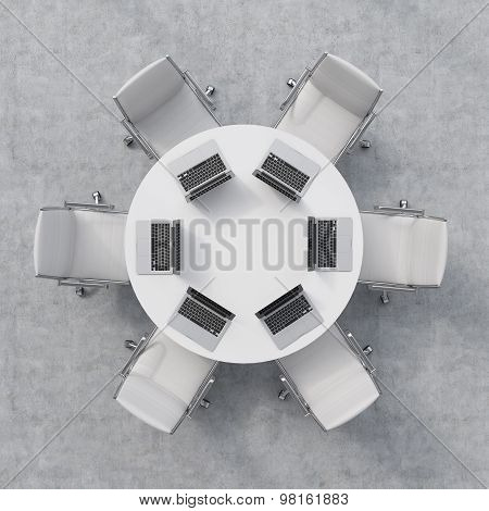 Top View Of A Conference Room. A White Round Table, Six Chairs. Six Laptops Are On The Table. Office