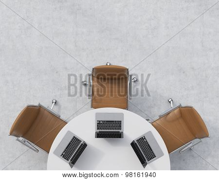 Top View Of A Half Of The Conference Room. A White Round Table, Three Brown Leather Chairs. Three La