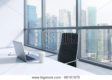A Workplace With Laptop And A Cap Of Coffee In A Modern Panoramic Office, Singapore City View. A Con