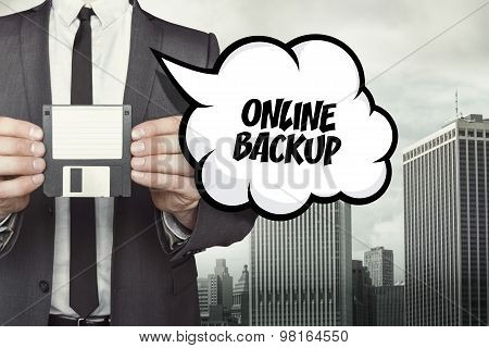 Online backup text on speech bubble with businessman holding diskette