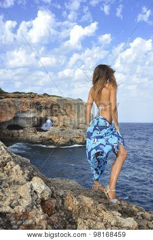 Woman Looking At Ocean Horizon On Rock Cliff By Sea Shore In Sarong Beach Wrap
