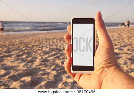 Man With Smartphone In His Hand On Beach. Point Of View.