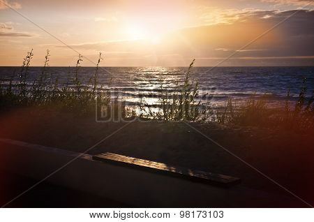 Empty Wooden Bench By The Sea At Sunset