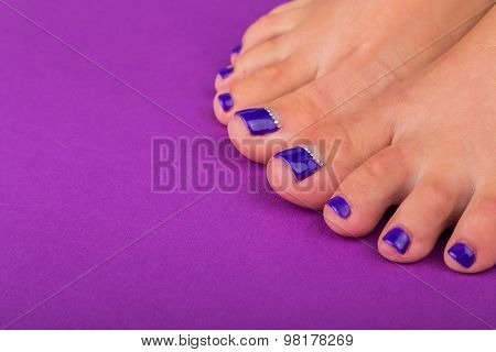 Beautiful female legs. blue nail pedicure.