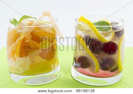 Peach And Raspberry Juices With Fruit Slices In A Crooked Glass On Green Background